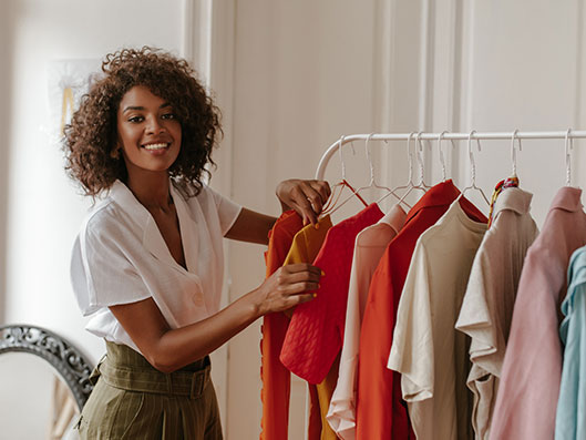smiling woman next to clothing rack