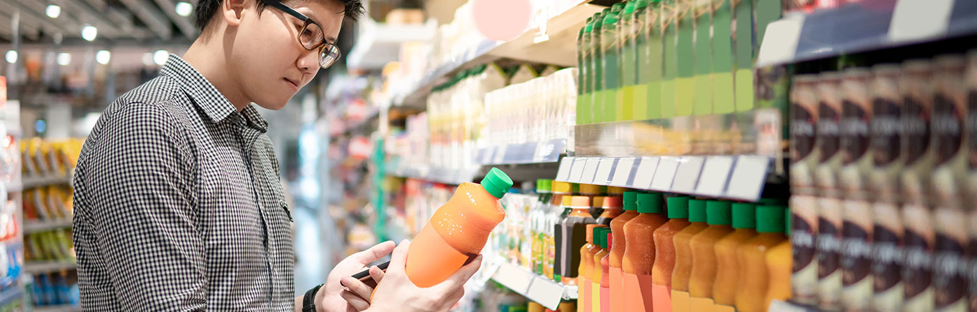 man grocery shopping in beverage aisle