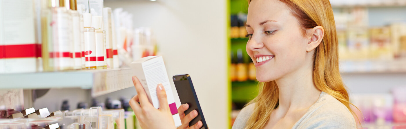 smiling woman scanning box in store with phone