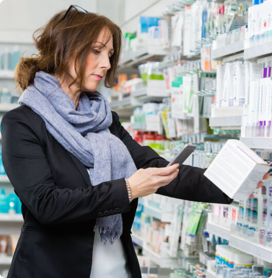 a woman scanning a box in a pharmacy with phone